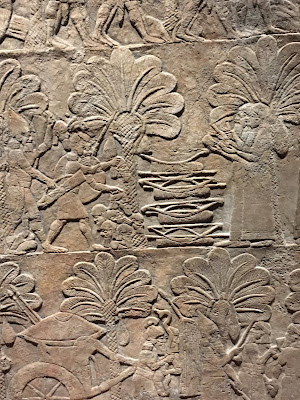 Assyrian stone frieze showing scribes making lists of bows and severed heads