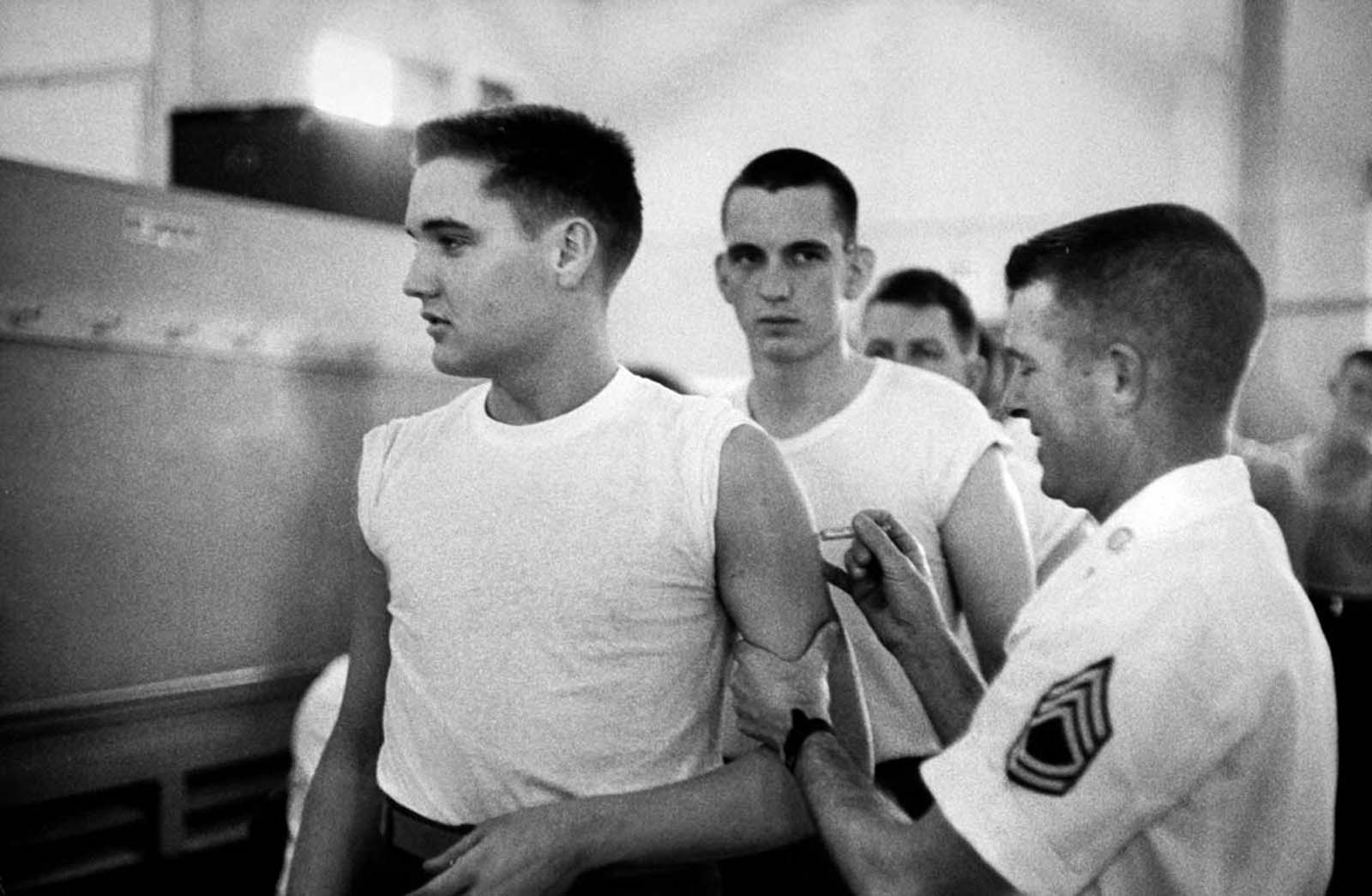 Presley in t-shirt, getting a shot from an Army doctor during his pre-induction physical at Kennedy Veterans Hospital.