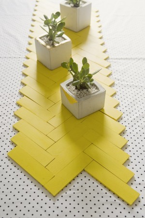 These yellow paint sticks assembled as a table runner look modern and funky.
