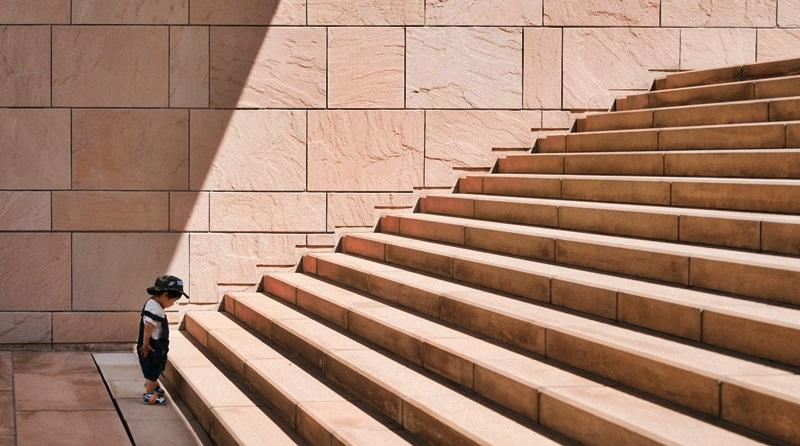 criança parada em frente aos degraus de uma escadaria