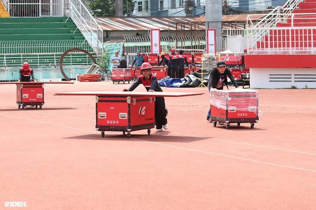 Các nhân viên lắp đặt đang chuyển những hòm thiết bị ra sân.