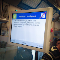 [Image: Information display onboard a Helsinki train, showing a transcript of an announcement along with the time of the day, current speed and other info.]