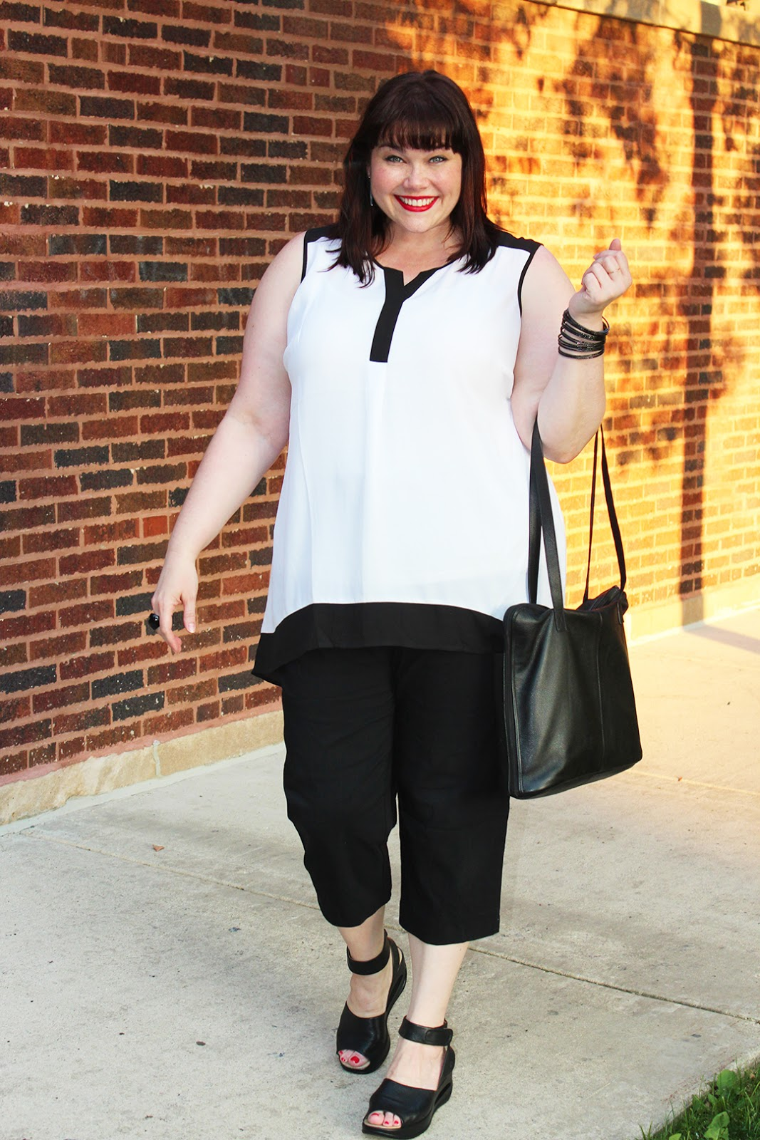 plus size blogger Amber from Style Plus Curves in a travel outfit from Avenue Plus; black capris and black and white tunic top