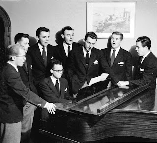 A black and white photograph of men singing around a piano.