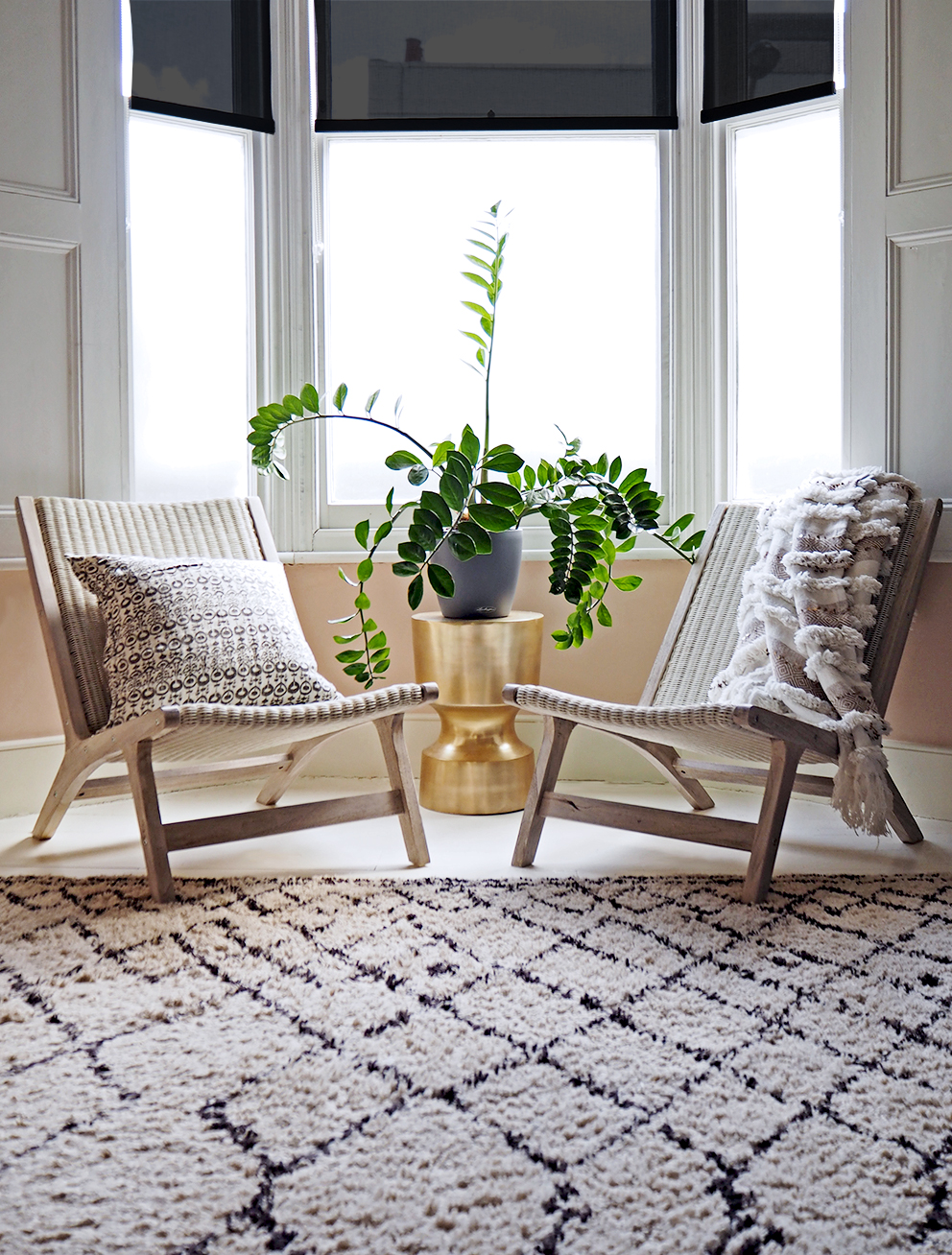 Outdoor Furniture Indoors - French For Pineapple Blog - wide shot of pair of wicker and teak chairs in bay window with zz plant on gold side table and moroccan throw and rug