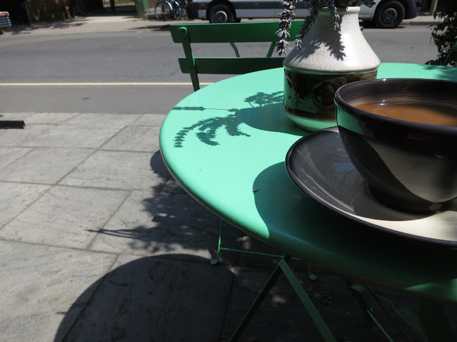 Coffee in cup on table with shadow of lavender in vase and shadow of pavement on pavement.