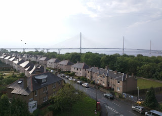 Wet rooftops glisten in the sunlight along Farquhar Terrace, with the Queensferry Crossing bridge in the background, South Queensferry, Scotland