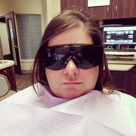 image of me in a dentist's chair wearing protective eyewear; my mouth is starting to slack from novocaine