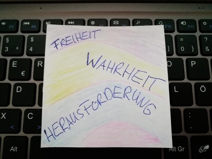 """Zettel mit den handgeschriebenen Worten """"Freiheit"""", """"Wahrheit"""", """"Herausforderung"""" liegt auf Laptop-Tastatur."""
