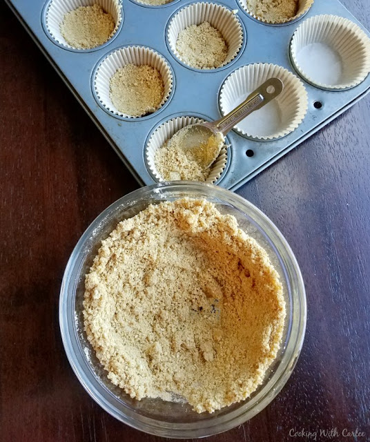putting graham cracker crust into cupcake liners for s'mores cupcakes