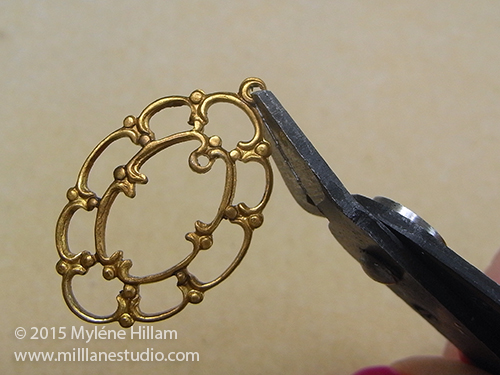 Trimming off the loop of the oval filigree using the button shank removers.