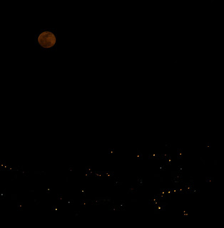 The moon above the town lights