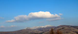 One cloud over a snow covered hilltop