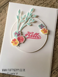 This image shows a white handmade card with pastel flowers and the sentiment Hello added using the Jar of Love stamp set by Stampin' Up!
