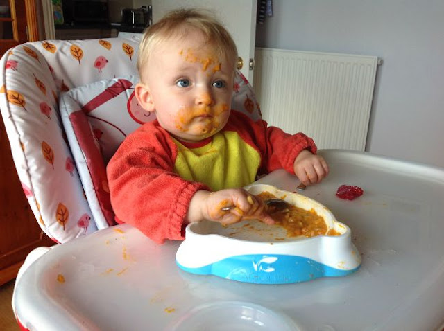 baby in highchair with spoon in hand and face covered in food