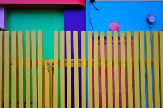 décoration d'extérieur colorée avec une barrière jaune et des murs bleu, vert, violet et rouge