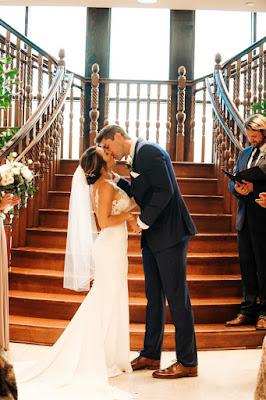 bride and groom kissing at stairway