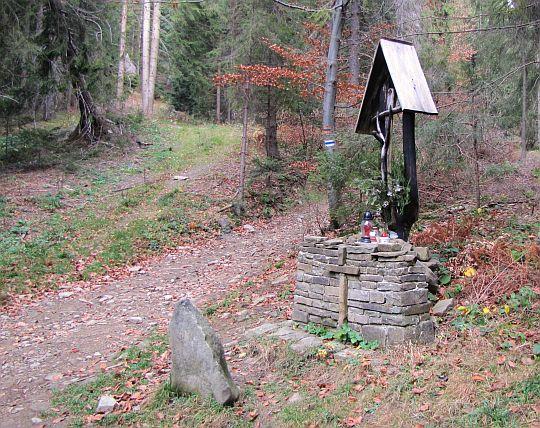 """Drewniany krzyż przy szlaku i kamień z inicjałami """"AK""""."""