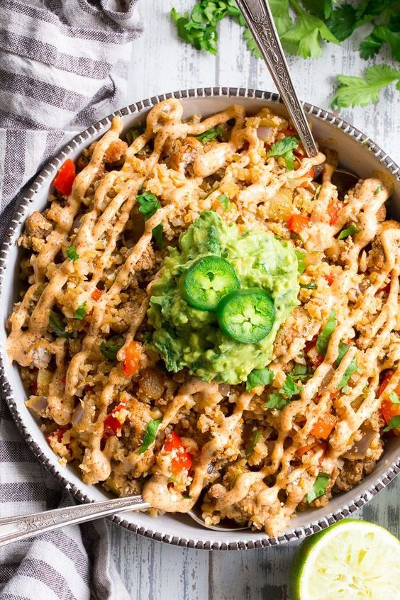 This Mexican Cauliflower Rice is packed with veggies, protein, and lots of flavor and spice! It's topped with an easy guacamole and chipotle ranch sauce for a tasty, filling meal that's Paleo, Whole30 compliant and keto friendly