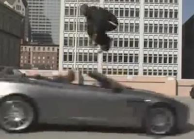 Kobe Bryant jumps over an Ashton Martin