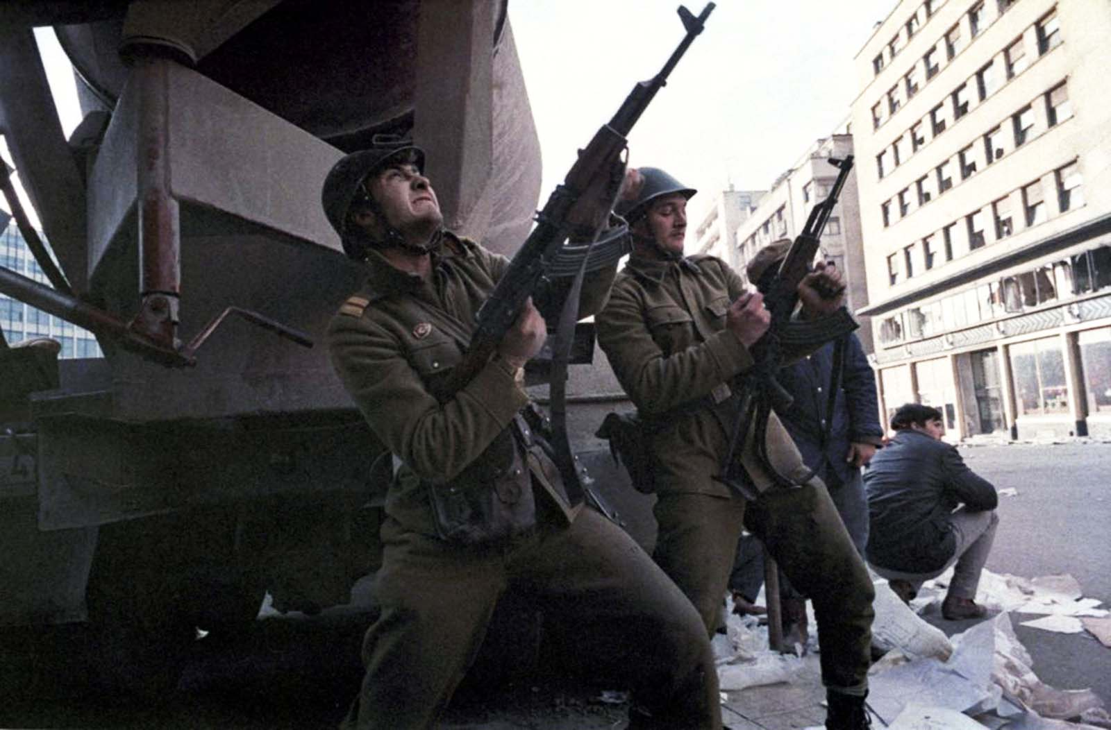 A Romanian soldier loads his automatic rifle as another shoots during heavy fighting against pro-Ceausescu troops in central Bucharest.