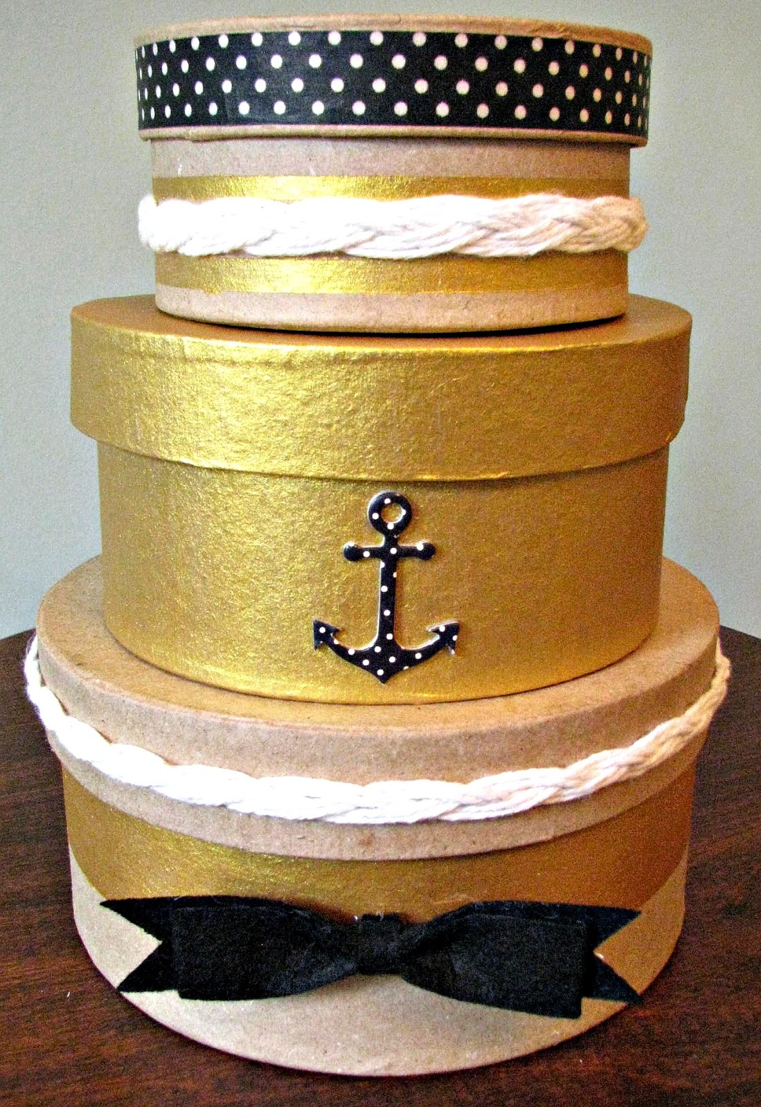 Decorative box with gold stripes, nautical rope, an anchor embellishment and black and white washi tape.