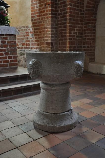Romański kościół w Altenkirchen - chrzcielnica zdobiona 4 twarzami
