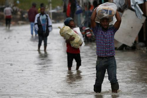 Hurricane Matthew: People carrying their remaining belongings through the flooded streets of Port-au-Prince, Haiti