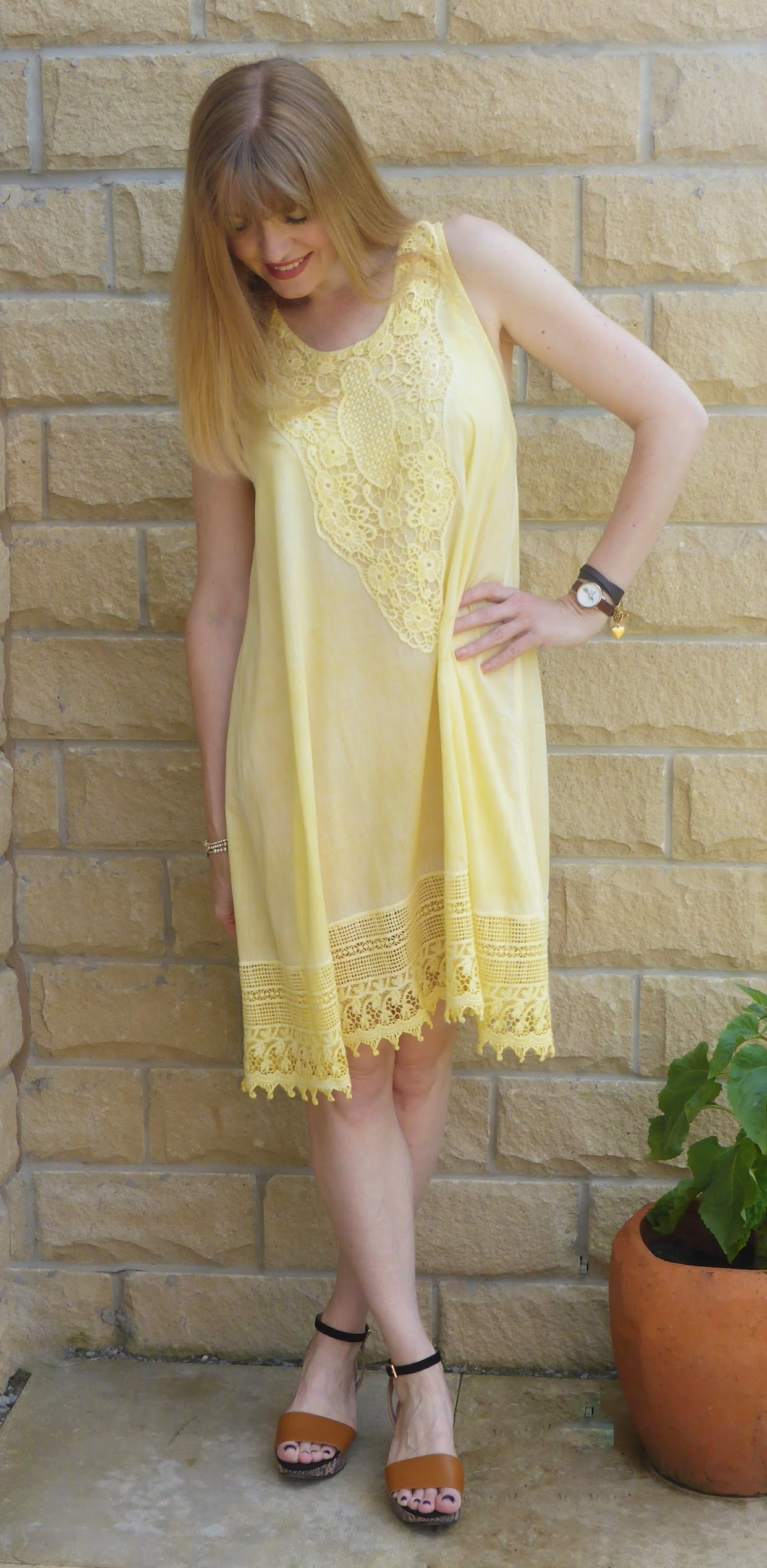 Over 40 blogger What Lizzy Loves wears yellow lace sundress with Clarks snake print wedge sandals