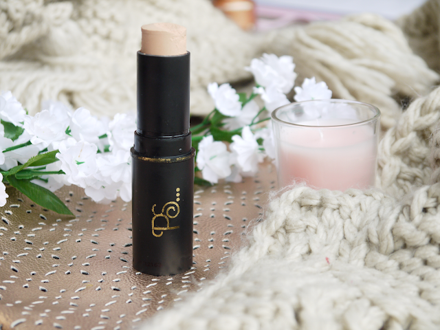 foundation stick in a black tube stood on a rose gold bag with cream woollen scarf and white flowers behind