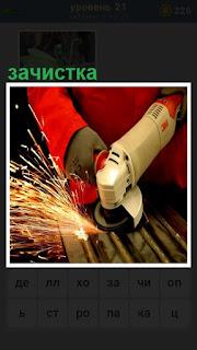рабочий производит зачистку железа специальным инструментом