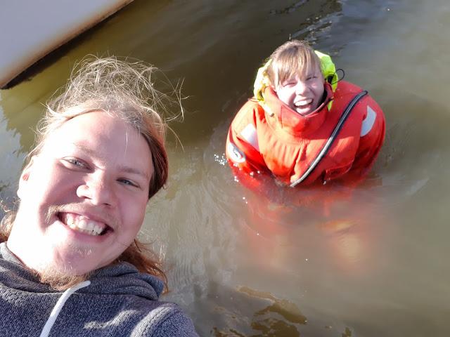 Kaksi nauravaa ihmistä. Toinen vedessä pelastautumispuvussa.