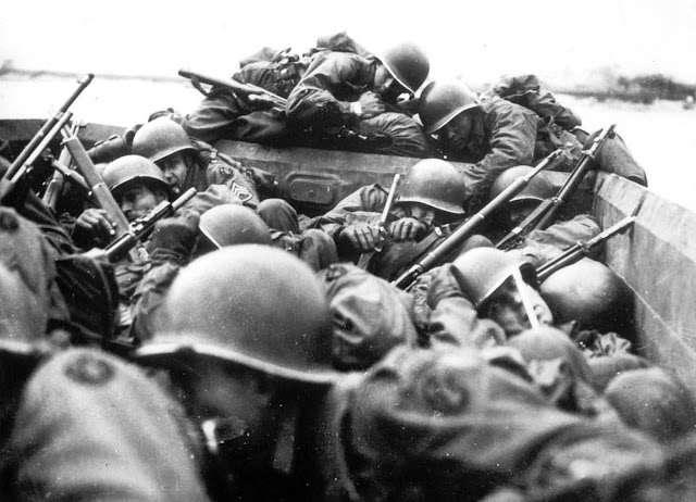 American soldiers aboard an assault boat huddle together as they cross the Rhine river at St. Goar, Germany, while under heavy fire from the German forces, in March of 1945.