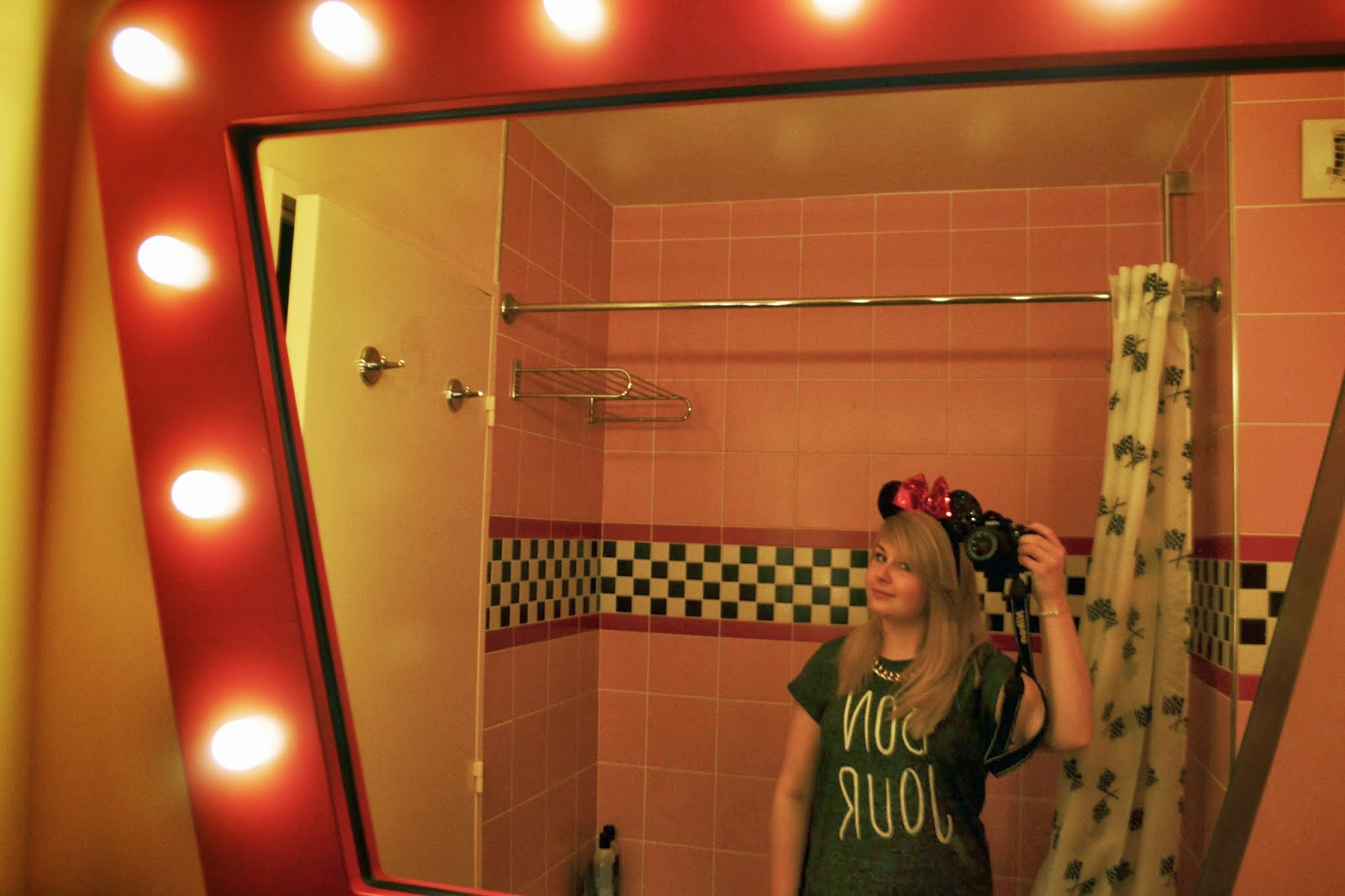 a mirror selfie in our hotel room. The bathroom mirror is lined with old style lightbulbs