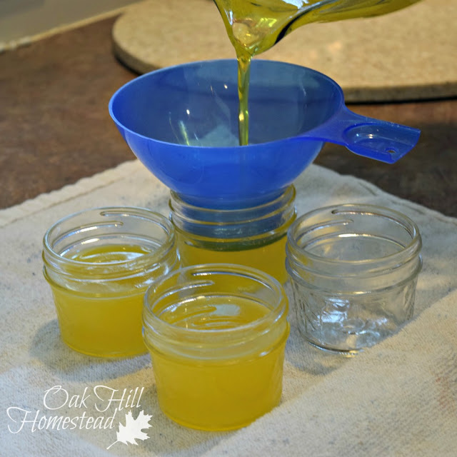 Pouring dandelion salve into jars