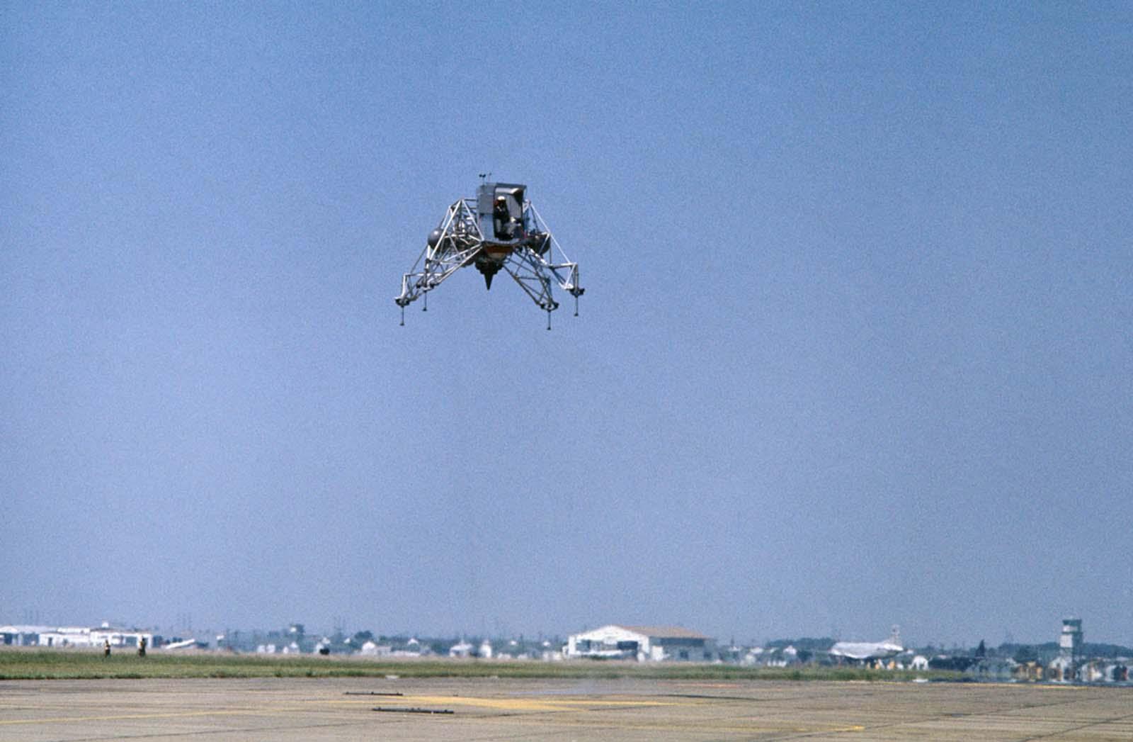 Legenda original: Praticar para o Big One em Ellington AFB, Texas. O Comandante da Apollo 11, Neil Armstrong, voa no Veículo de Treinamento da Lunar Landing em preparação para a tentativa de pouso lunar em julho. O vôo durou cinco minutos, durante os quais Armstrong fez duas decolagens e aterrissagens. Ele voou a nave a uma altitude de cerca de 300 pés.