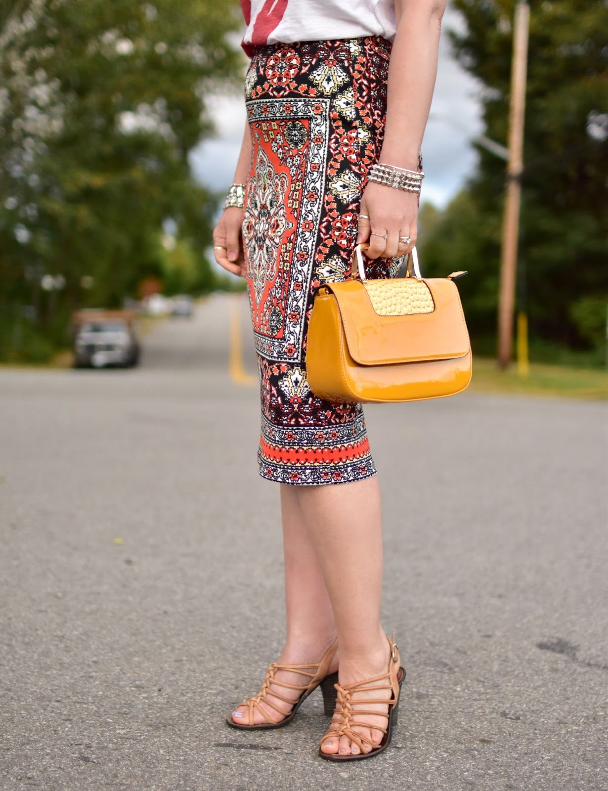 patterned pencil skirt, strappy nude sandals, and yellow patent mini bag