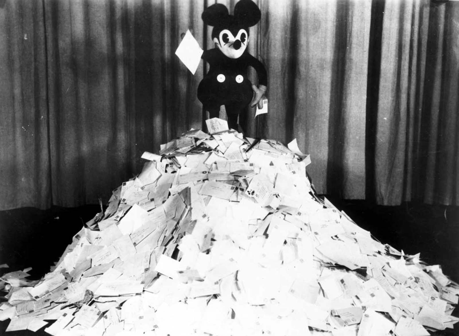 Mickey on top of a pile of letters that he received from fans. 1928.
