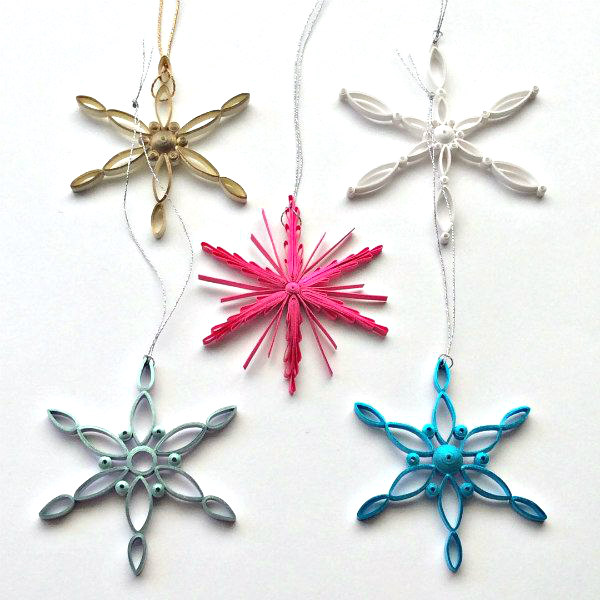 quilled snowflake ornaments made with gold, white, and brightly colored metallic strips