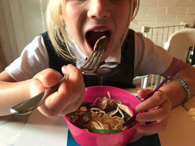 A girl in school uniform eating a beef stir fry made with an easy recipe
