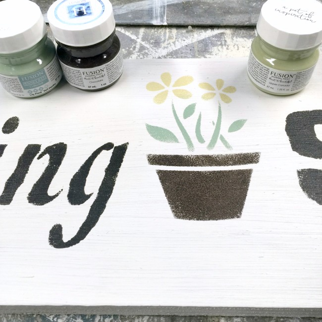 Stenciling a garden sign with sample paints