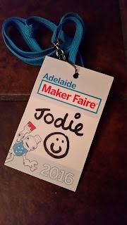 "2017's exhibitor pass, made of cardboard. Printed on it are the words ""Adelaide Maker Faire 2016"" with a picture of Sam Robot. In black texta is the name ""Jodie"" and a smiley face."