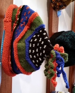 A knitted beanie in orange, blue, green and topped with a white dots on a black background which sprouts curlicues of all colours at the top.  The main stripes are in stockinette and divided by narrower stripes of garter stitch.