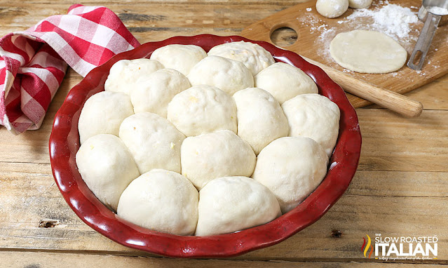 """""""bombs"""" of stuffed bread dough in red pie plate, ready for baking"""