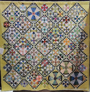 Steam Punk (airplane propeller) quilt blocks grouped in fours with sawtooth sashing of dark blue and white is bordered with chartreuse