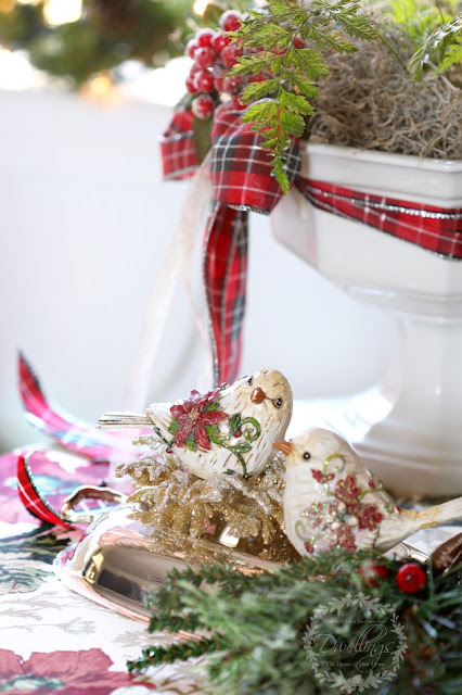 Christmas birds sitting on a silver tray with greenery and berries.
