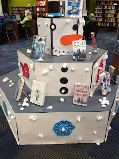 Book display showcases a snowman to decorate and books about snow and winter.