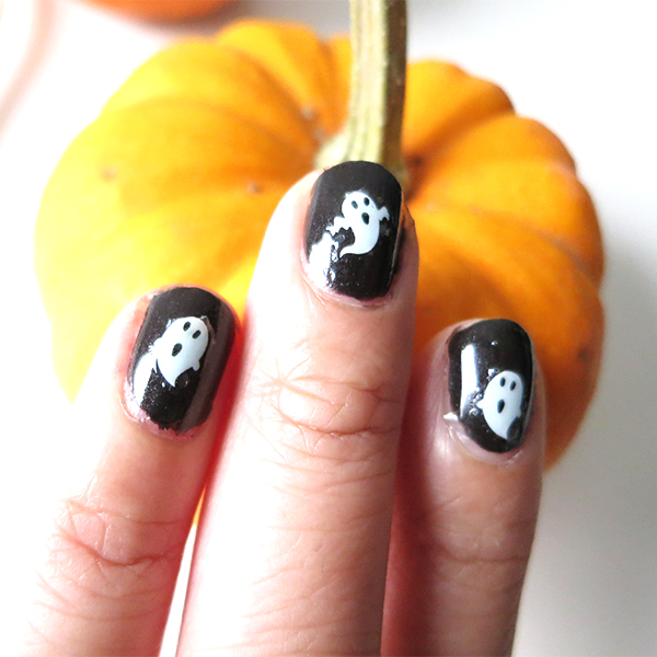 Halloween-inspired manicure with black nail polish and white ghosts using Kiss Nail Art Stickers Halloween Edition