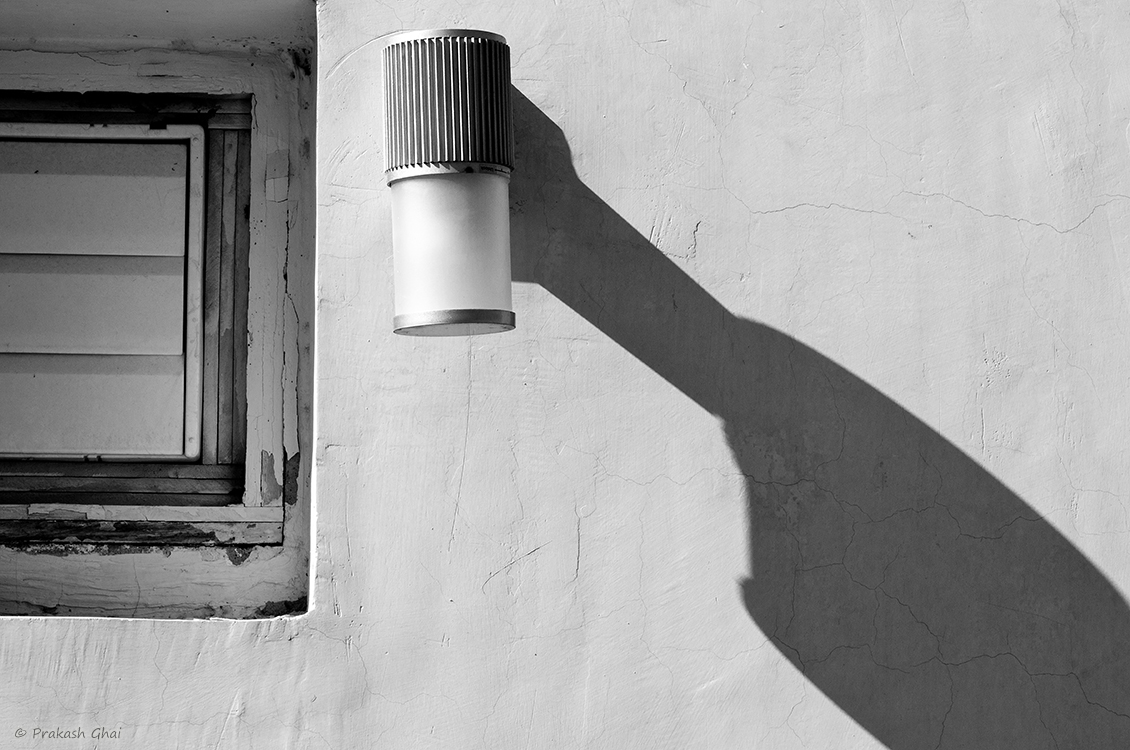 A minimalist photo of Long Shadow of a light mounted on the wall.