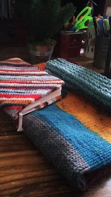 Three finished objects or knitting projects; a Strickplaner cover, a cowl and a pair of fingerless mitts.